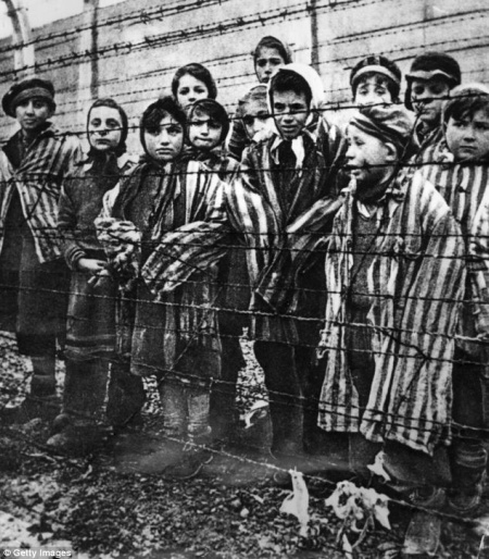 Children behind a barbed wire fence at the infamous concentration camp at Auschwitz in southern Poland